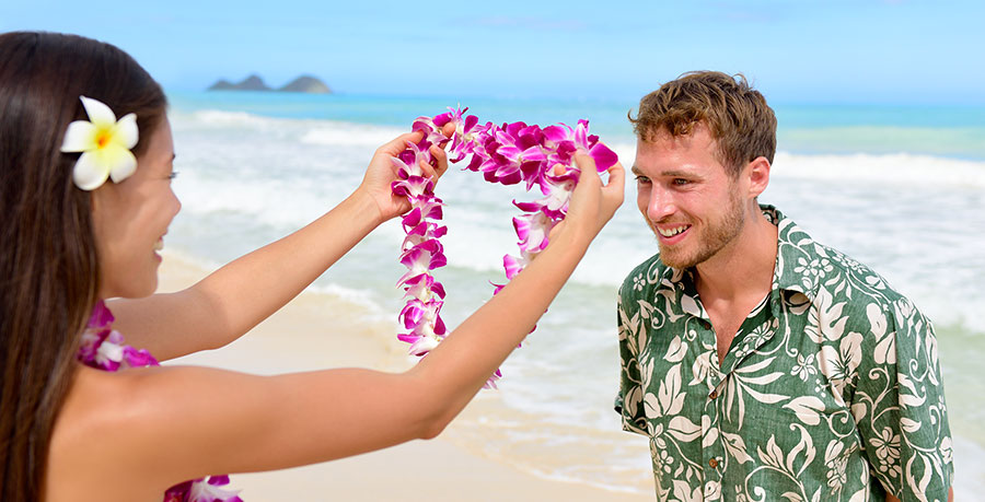 Man receiving a lei around his neck on the beach