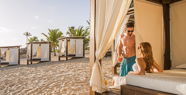 A couple enjoys a Balienese bed on the beach at Hard Rock Hotel & Casino Punta Cana.