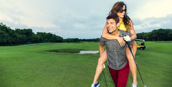 A woman gets a piggyback ride by her boyfriend or husband on a golf course.