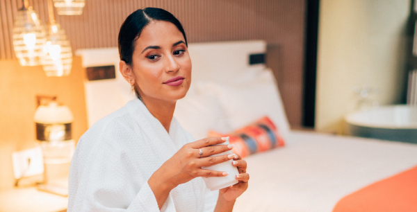 A woman in a white robe sits on the hotel bed with a mug in her hands.