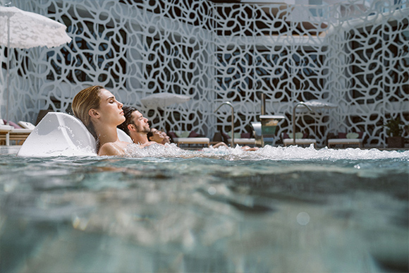 Two couples lounge in a hydropool in the Rock Spa.