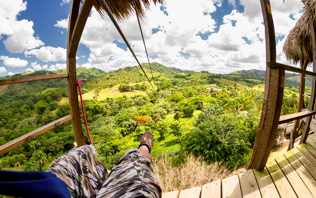 Man peers down over the tree tops before he glides on the zip line during his Bavaro Runners tour.