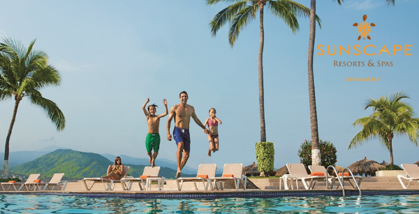A dad, son, and daughter are mid-jump into a pool with mom in a chair watching them.