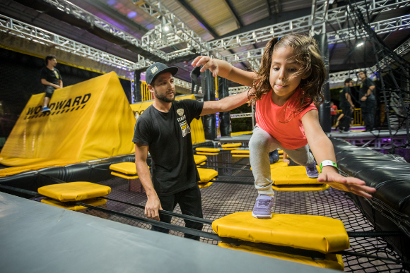 A little girl jumps from a floating disc in an obstacle course called WreckTangle with the help of a Woodward Riviera Maya staff member.